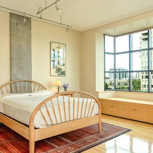 Inspiration for a contemporary light wood floor bedroom remodel in Portland with beige walls
