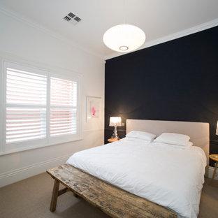 Пример оригинального дизайна: большая хозяйская спальня в стиле рустика с черными стенами, ковровым покрытием, стандартным камином, фасадом камина из штукатурки и бежевым полом