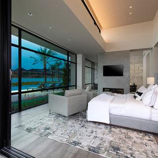 Diseño de dormitorio principal, actual, extra grande, con paredes grises, suelo de madera clara, chimenea de doble cara, marco de chimenea de hormigón y suelo gris