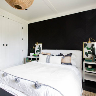Inspiration for a farmhouse bedroom in Sacramento with black walls and black floors.