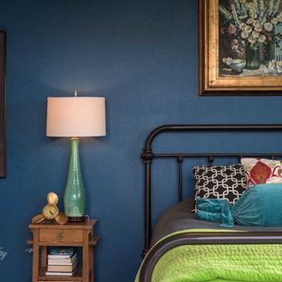 Modelo de dormitorio de estilo de casa de campo, de tamaño medio, con paredes azules, suelo de madera pintada, chimeneas suspendidas, marco de chimenea de metal y suelo blanco