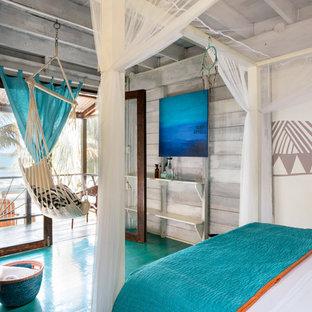Immagine di una camera da letto tropicale con pareti multicolore e pavimento in legno verniciato