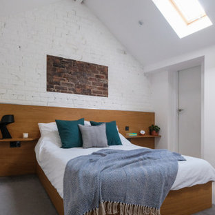 Mid-sized modern master bedroom in West Midlands with white walls, carpet, grey floor, vaulted and brick walls.