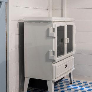На фото: маленькая гостевая спальня в скандинавском стиле с белыми стенами, полом из ламината, печью-буржуйкой и серым полом с