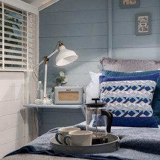 Imagen de habitación de invitados nórdica, pequeña, con paredes azules, suelo laminado, estufa de leña y suelo gris
