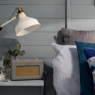 Foto de habitación de invitados nórdica, pequeña, con paredes azules, suelo laminado, estufa de leña y suelo gris