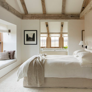 На фото: хозяйские спальни среднего размера в стиле кантри с белыми стенами, ковровым покрытием и бежевым полом