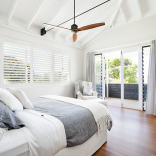 Inspiration for a beach style master bedroom in Central Coast with white walls and medium hardwood floors.
