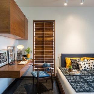 Ispirazione per una camera degli ospiti etnica con pareti bianche e pavimento nero