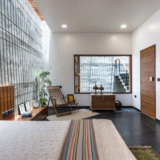 Foto di una grande camera degli ospiti etnica con pareti bianche, pavimento in cemento e pavimento grigio