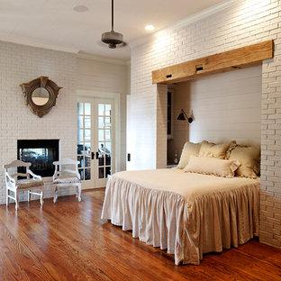 Modelo de dormitorio de estilo de casa de campo con paredes grises, suelo de madera oscura, chimenea de doble cara y marco de chimenea de ladrillo