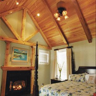Imagen de dormitorio principal, rústico, extra grande, con paredes verdes, moqueta, chimenea tradicional y marco de chimenea de madera