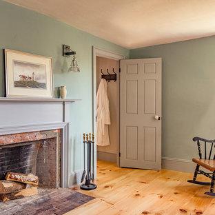 Diseño de dormitorio principal, de estilo de casa de campo, de tamaño medio, con paredes azules, suelo de madera clara, chimenea tradicional y marco de chimenea de ladrillo