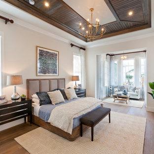 Ejemplo de dormitorio principal, tropical, extra grande, con paredes beige, suelo de madera en tonos medios y suelo marrón