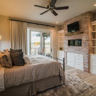 Ejemplo de habitación de invitados rural, de tamaño medio, con paredes grises, suelo de madera clara, chimenea lineal, marco de chimenea de ladrillo y suelo beige