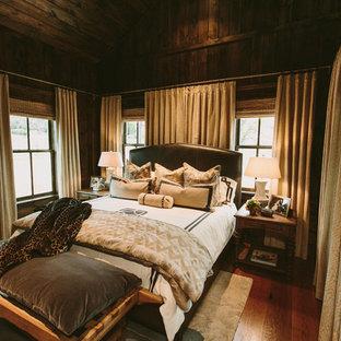 Modelo de dormitorio principal, rural, de tamaño medio, sin chimenea, con paredes marrones y suelo de madera oscura
