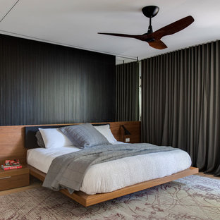 This is an example of a mid-sized contemporary master bedroom in Sydney with white walls, light hardwood floors and beige floor.