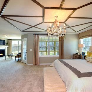 Неиссякаемый источник вдохновения для домашнего уюта: огромная хозяйская спальня в классическом стиле с серыми стенами, ковровым покрытием, стандартным камином и фасадом камина из дерева
