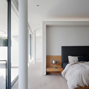 This is an example of a modern master bedroom in Melbourne with white walls, light hardwood floors and beige floor.