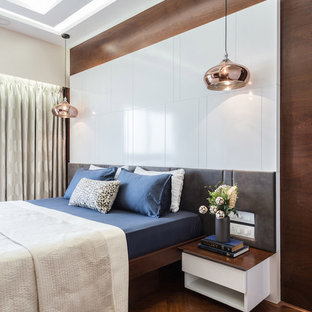 Photo of a contemporary master bedroom in Mumbai with brown walls, dark hardwood flooring and brown floors.