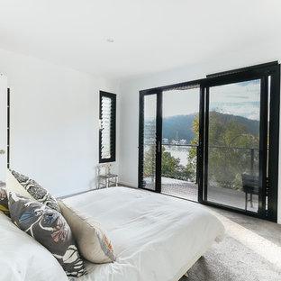 Ejemplo de dormitorio tipo loft, actual, pequeño, sin chimenea, con paredes blancas, moqueta, marco de chimenea de ladrillo y suelo gris