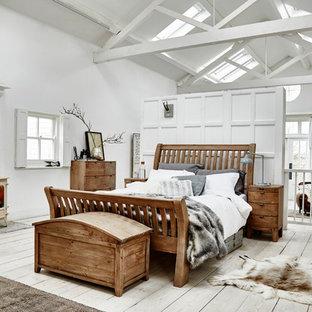 Imagen de dormitorio principal, rústico, grande, con suelo de madera clara, estufa de leña y suelo blanco