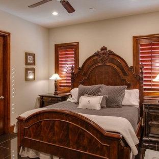 Ejemplo de habitación de invitados tradicional, de tamaño medio, sin chimenea, con paredes beige, suelo de piedra caliza y suelo negro