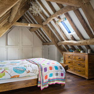 Country guest bedroom in Wiltshire with dark hardwood flooring, white walls and brown floors.