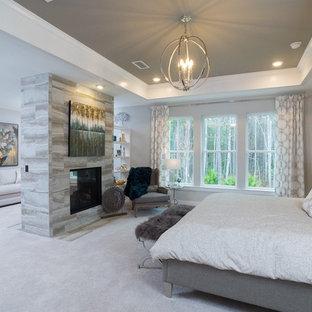 Diseño de dormitorio principal, ecléctico, grande, con paredes beige, moqueta, chimenea de doble cara, marco de chimenea de piedra y suelo beige