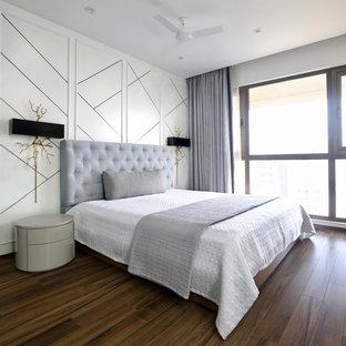 ムンバイのコンテンポラリースタイルのおしゃれな客用寝室 (白い壁、濃色無垢フローリング、茶色い床) のレイアウト