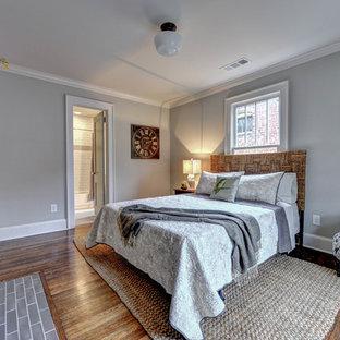 Modelo de habitación de invitados tradicional, pequeña, con paredes grises, suelo de madera en tonos medios, chimenea tradicional y marco de chimenea de ladrillo
