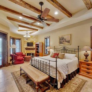 Идея дизайна: большая хозяйская спальня в классическом стиле с бежевыми стенами, полом из травертина, стандартным камином, фасадом камина из плитки и коричневым полом