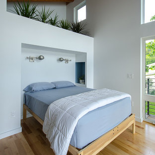 Photo of a mid-sized contemporary master bedroom in Burlington with white walls, medium hardwood floors and yellow floor.
