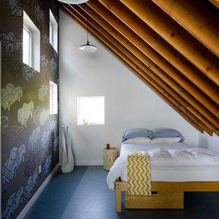 Modelo de dormitorio tipo loft, contemporáneo, pequeño, con paredes blancas, suelo laminado y suelo azul