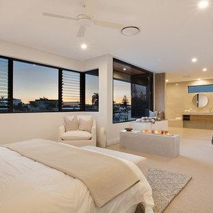 Idee per una grande camera matrimoniale minimalista con pareti bianche, moquette, camino bifacciale, cornice del camino in cemento e pavimento beige