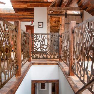 Foto di una camera matrimoniale stile rurale di medie dimensioni con pareti bianche, parquet scuro, stufa a legna e pavimento marrone