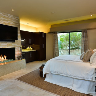 Diseño de habitación de invitados contemporánea, grande, con paredes beige, suelo de travertino, chimenea tradicional y marco de chimenea de baldosas y/o azulejos