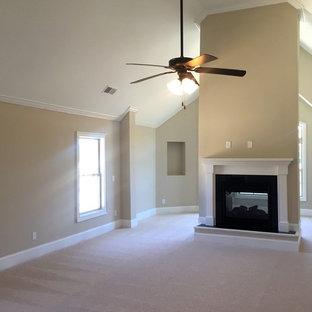 Imagen de dormitorio principal, de estilo americano, grande, con paredes beige, moqueta, chimenea de doble cara y marco de chimenea de madera
