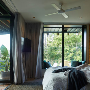 This is an example of a contemporary bedroom in Brisbane with brown walls, carpet and brown floor.
