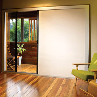 Example of a mid-sized minimalist guest medium tone wood floor and brown floor bedroom design in Hawaii with beige walls and no fireplace