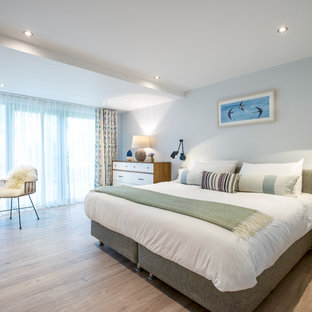 Photo of a large nautical master bedroom in Cornwall with grey walls, light hardwood flooring and beige floors.