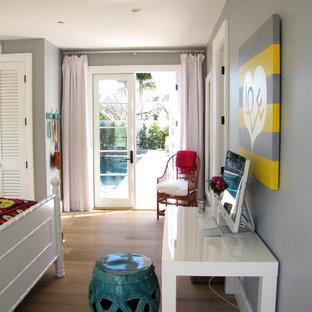 Example of a coastal bedroom design in Orange County with gray walls