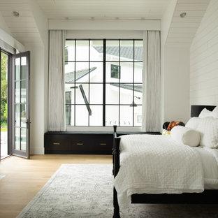 ボイシのカントリー風おしゃれな寝室 (白い壁、無垢フローリング、標準型暖炉、レンガの暖炉まわり、茶色い床、三角天井、塗装板張りの壁)