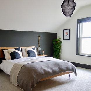 Modelo de habitación de invitados escandinava, grande, con paredes blancas, moqueta, chimenea tradicional, marco de chimenea de metal y suelo gris