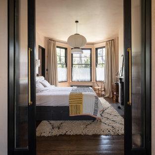 Diseño de dormitorio bohemio con paredes rosas, suelo de madera oscura y suelo marrón