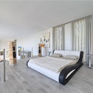 Ejemplo de dormitorio tipo loft, actual, con paredes blancas y suelo gris