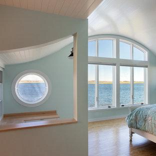 Modelo de dormitorio principal, costero, de tamaño medio, con paredes azules, suelo de madera clara, chimenea lineal y marco de chimenea de madera
