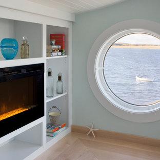 Foto de dormitorio principal, marinero, de tamaño medio, con paredes azules, suelo de madera clara, chimenea lineal y marco de chimenea de madera