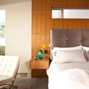 Foto di una camera da letto minimalista con pareti bianche e pavimento in cemento