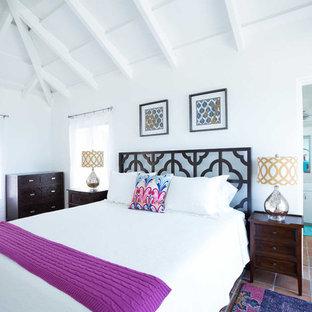 Imagen de dormitorio tropical, grande, con paredes blancas y suelo de baldosas de terracota